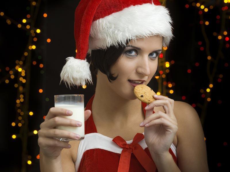 Bild zu Frau im Weihnachtskostüm isst Keks
