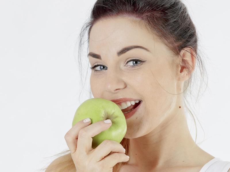 Bild zu Eine Frau ist einen Apfel