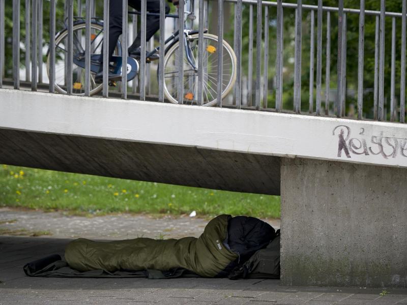 Bild zu Ein Obdachloser liegt unter einer Brücke
