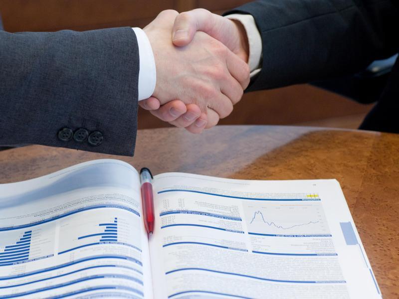 Bild zu Handschlag und Firmenunterlagen