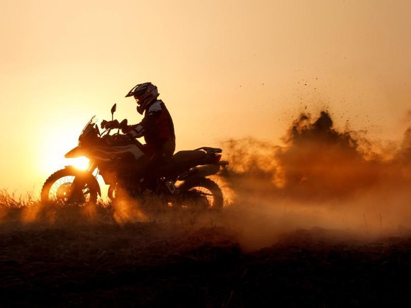 Bild zu Motorradfahrer bei Sonnenuntergang