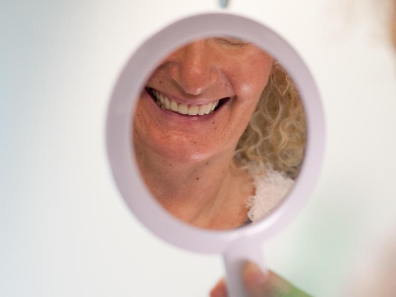 Bild zu Frau lächelt sich im Spiegel an