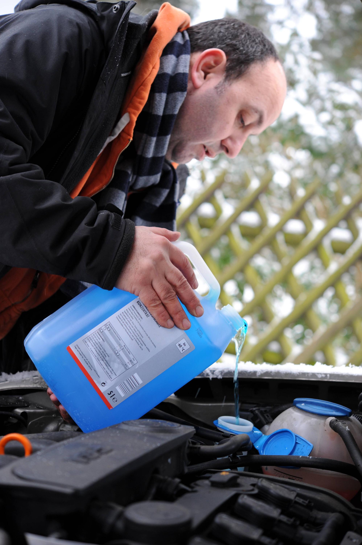 Bild zu Mann gießt Frostschutz in Scheibenwischanlage
