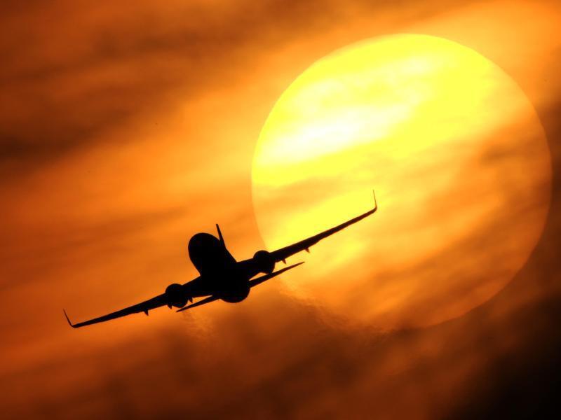 Bild zu Ein Flugzeug vor der untergehenden Sonne