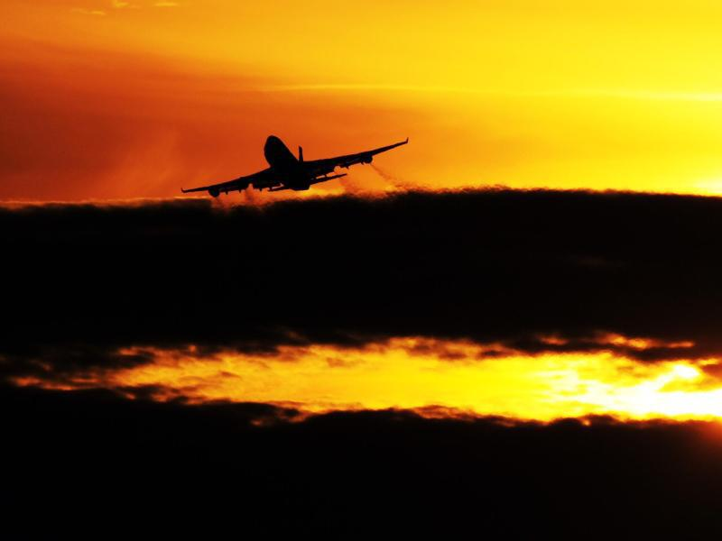 Bild zu Ein Flugzeug startet während des Sonnenuntergangs