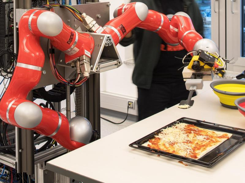 Bild zu Roboter verteilt Käse auf einer Pizza