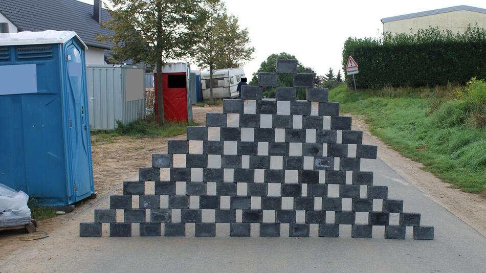 Unbekannte bauen Pyramide aus Pflastersteinen auf Straße
