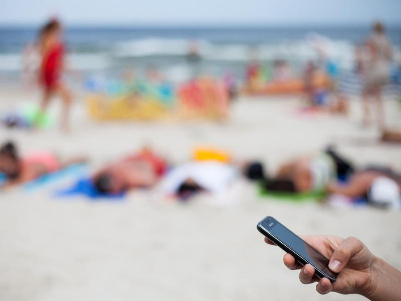 Bild zu Eine Frau mit Smartphone am Strand
