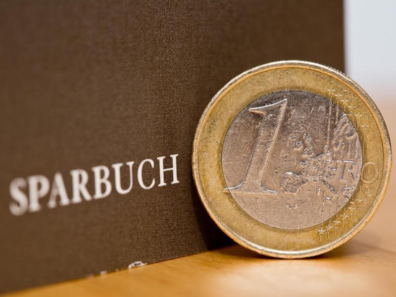 Bild zu Ein-Euro-Münze liegt neben Sparbuch