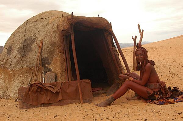 Bild zu Ein Frau des traditionellen Himba-Volkes sitzt vor ihrer Hütte.