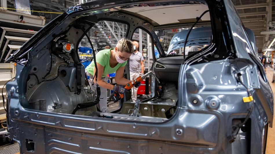 Eine Mitarbeiterin von Volkswagen Sachsen montiert einen ID.3.