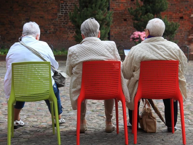 Bild zu Rentner sitzen auf Stühlen im Freien