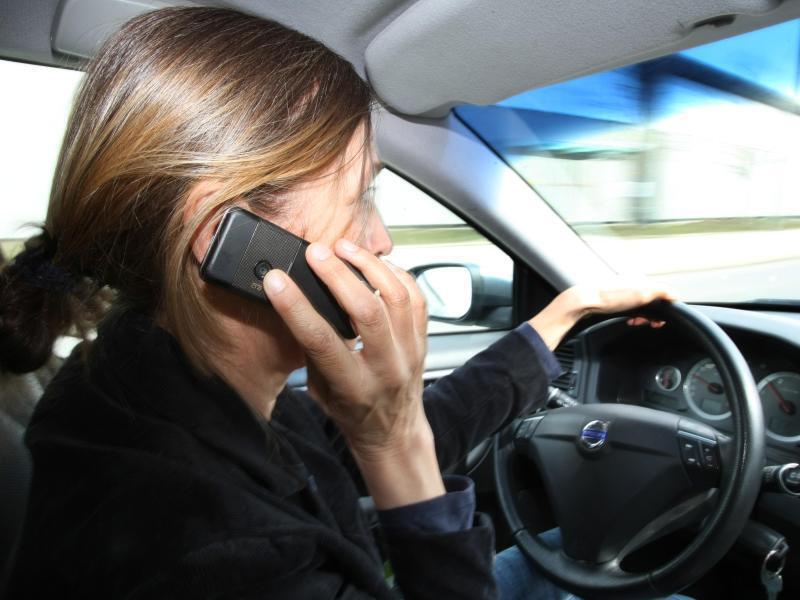 Bild zu Autofahrerin mit Handy am Steuer