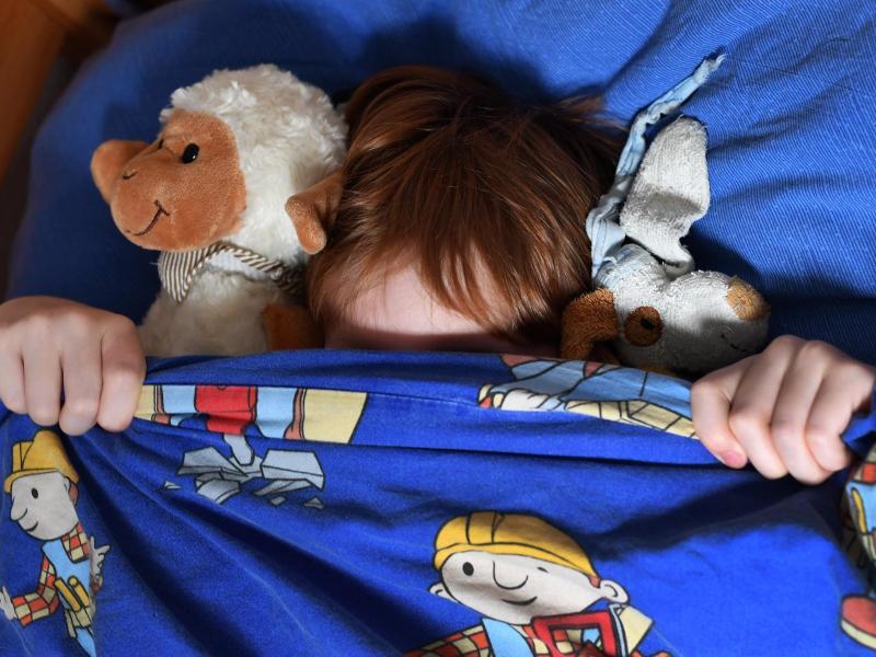 Bild zu Kind zieht Kopf unter die Bettdecke
