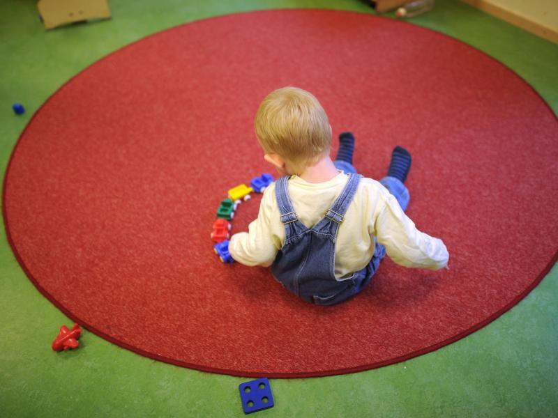 Bild zu Kind sitzt auf einem Teppich