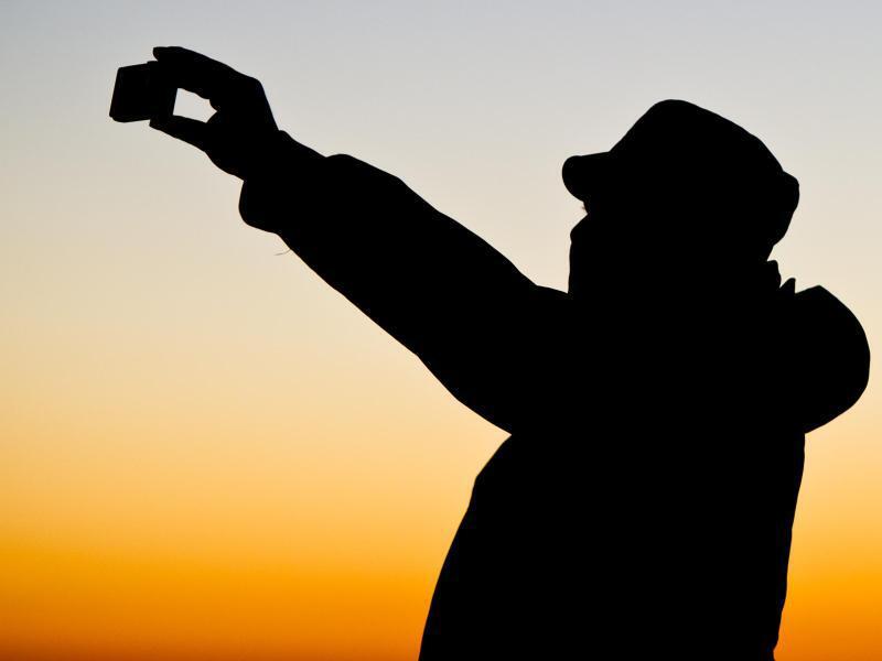 Bild zu Mann fotografiert mit dem Smartphone