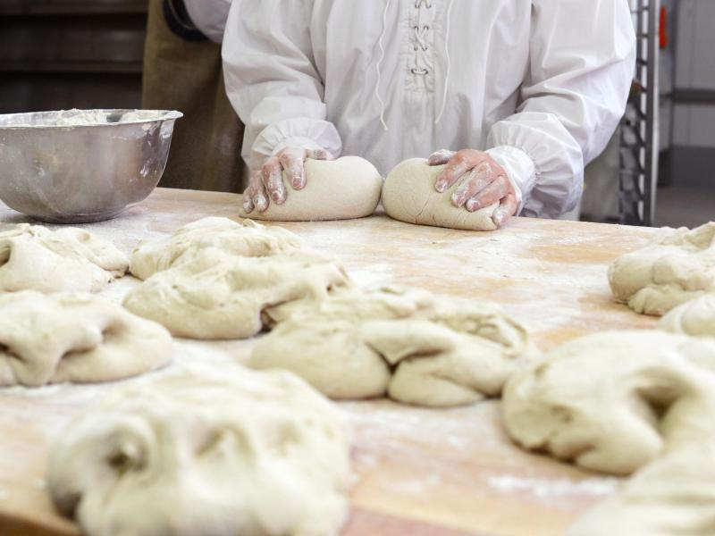 Bild zu Ein Bäcker knetet Teiglinge