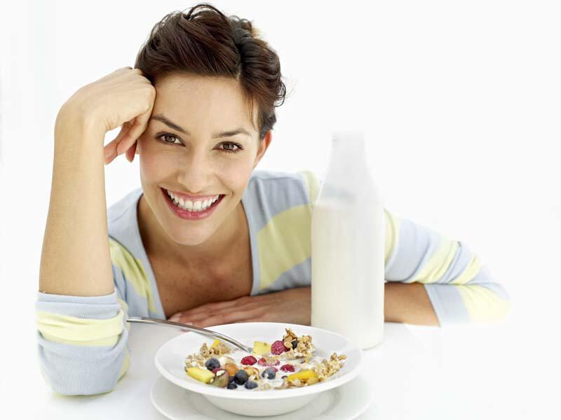 Bild zu Schöne Frau sitzt vor einem Teller Müsli