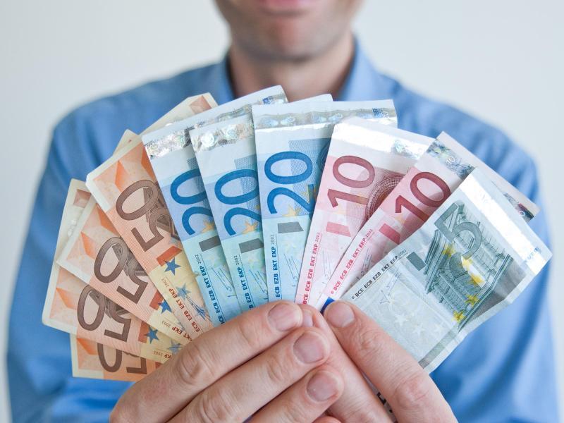 Bild zu Ein Mann zeigt Geldscheine