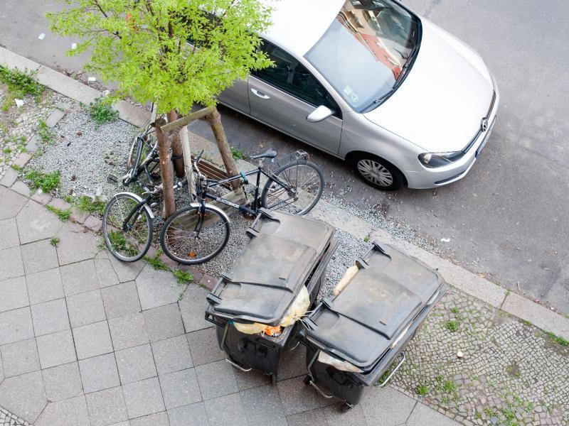 Bild zu Parkendes Auto neben Mülltonnen