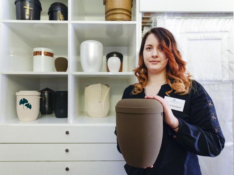Bild zu Carolin Dumbeck mit einer Urne