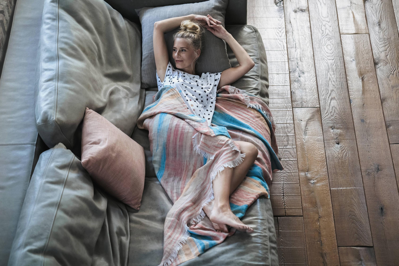 Bild zu Frau liegt auf Couch