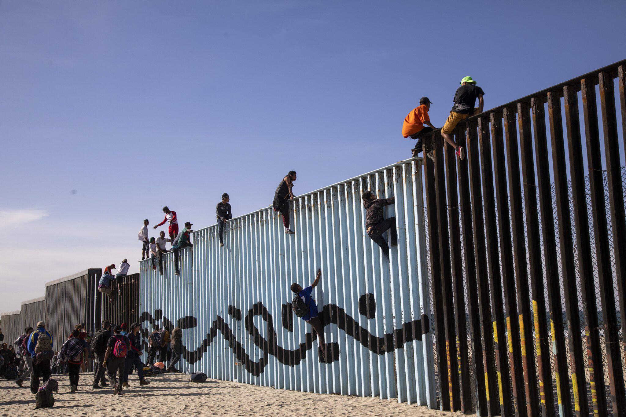 Bild zu Mitglieder der Migrantenkarawane erreichen die Grenzmauer
